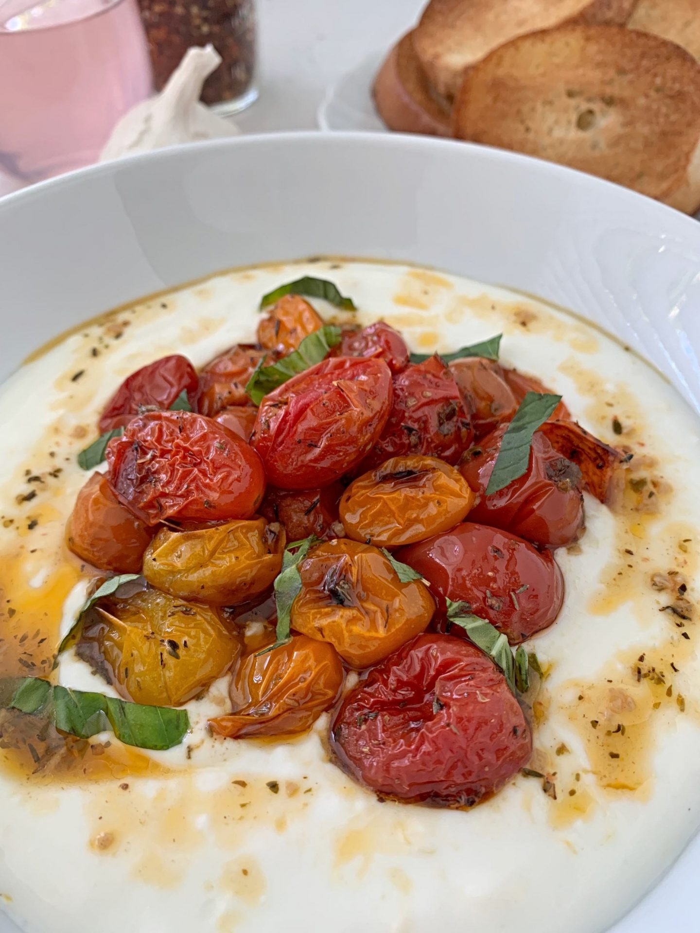 Close up of roasted summer cherry tomatoes with spices and fresh basil, sitting atop a bed of cool, creamy, tangy yogurt.